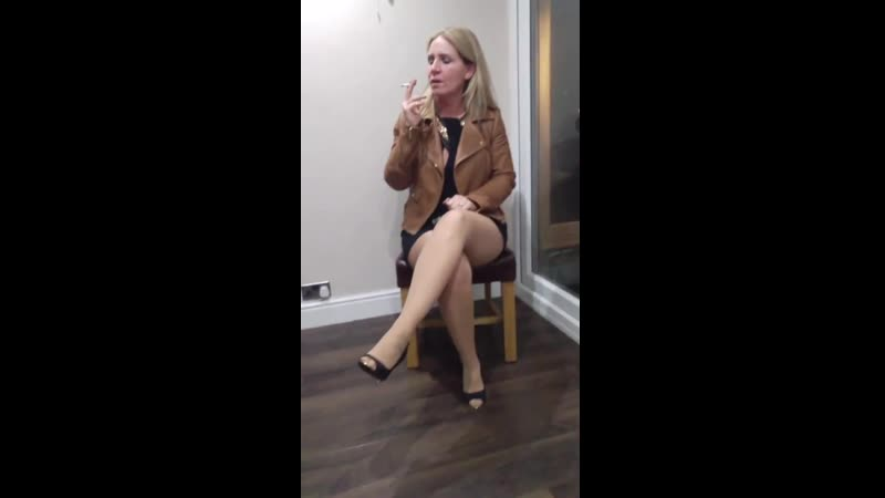 Lucy in a Flashback Friday video smoking in little black dress pantyhose tights tan leather jacket